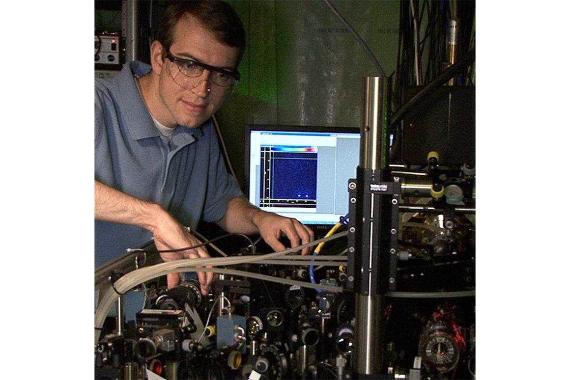 NIST postdoctoral researcher David Hanneke at the laser table used to demonstrate the first universal programmable processor. The monitor displays a colorized image of the two beryllium ions that hold information in the processor (Photo: J. Burrus/NIST)