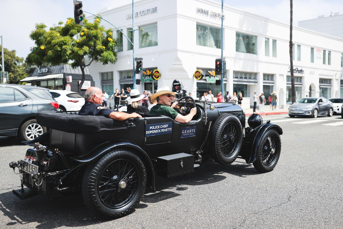 Event founder Bruce Meyer chauffeurs Beverly Hills Police Chief Dominick Rivetti in the 2021 Beverly Hills Tour d'Elegance in his 1929 Bentley 4½ Litre Tourer. Rivetti has 51 years of service in law enforcement behind him.