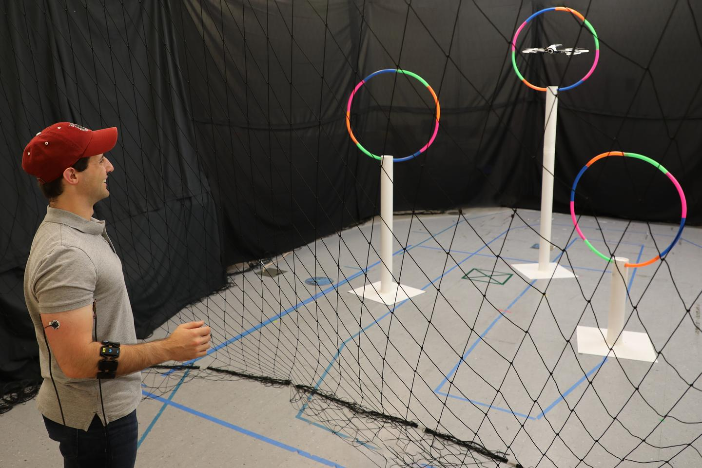 Lead author Joseph DelPreto uses the Conduct-A-Bot system to guide a drone through hoops