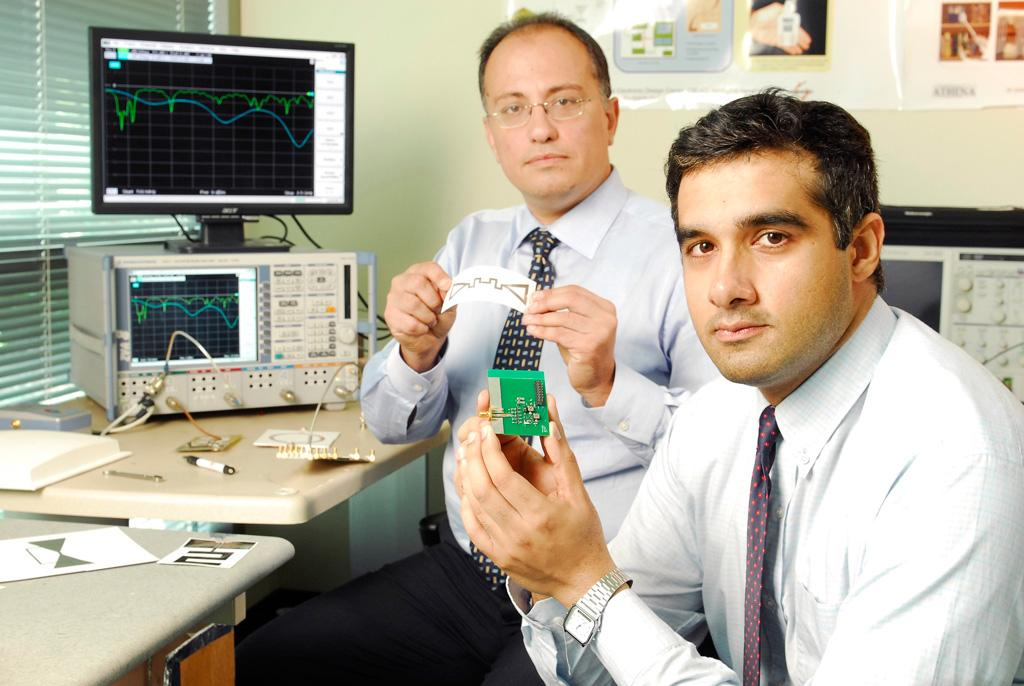 Georgia Tech graduate student Rushi Vyas (front) holds a prototype energy-scavenging device, while School of Electrical and Computer Engineering professor Manos Tentzeris displays a miniaturized flexible antenna (Image: Gary Meek)