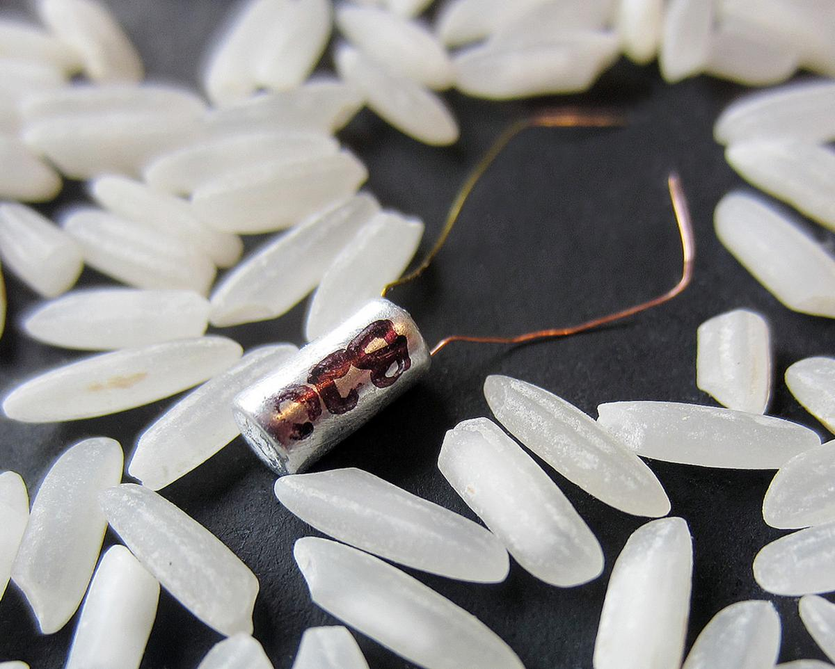 One of the new micro-batteries, amongst grains of rice for scale