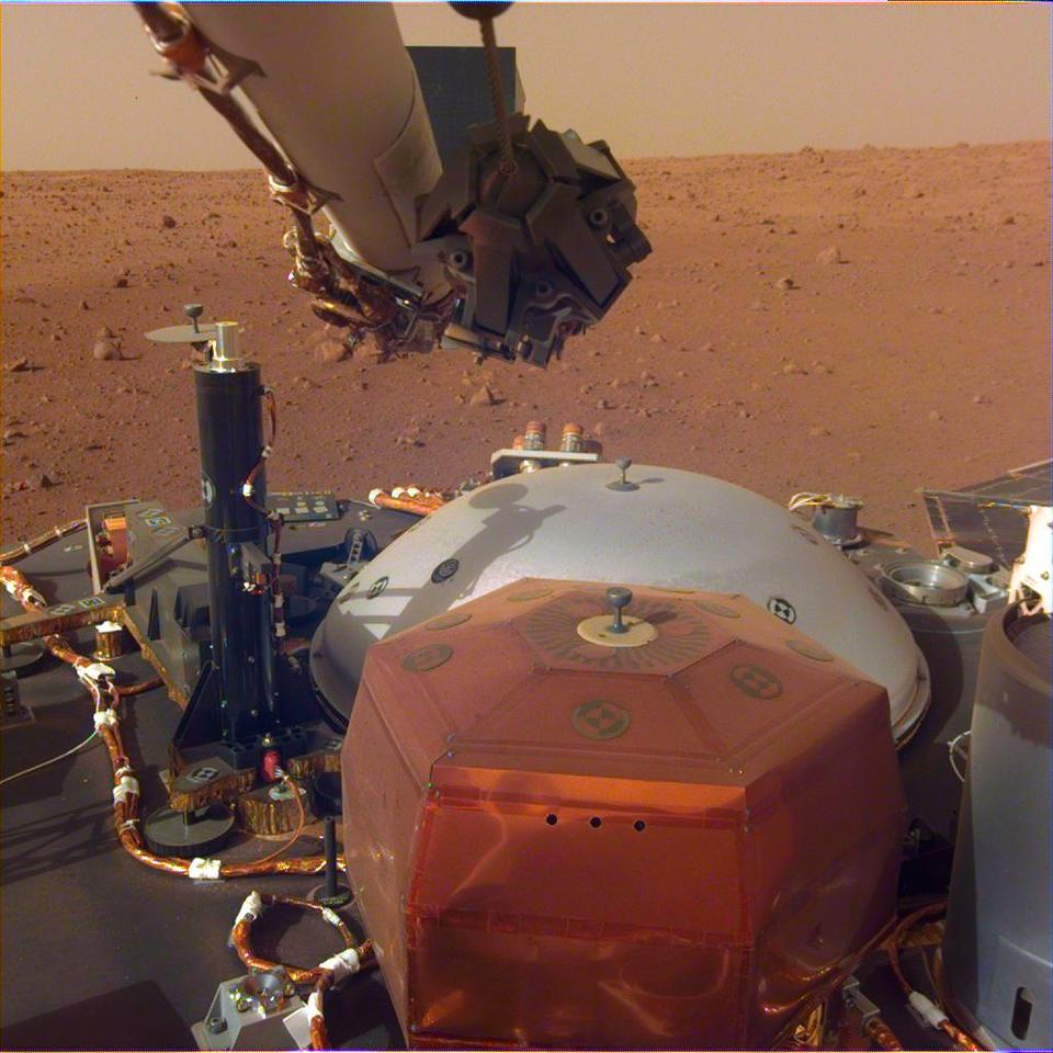 Image from InSight's robotic-arm-mounted Instrument Deployment Camera showing the instruments on the spacecraft's deck with Elysium Planitia in the background