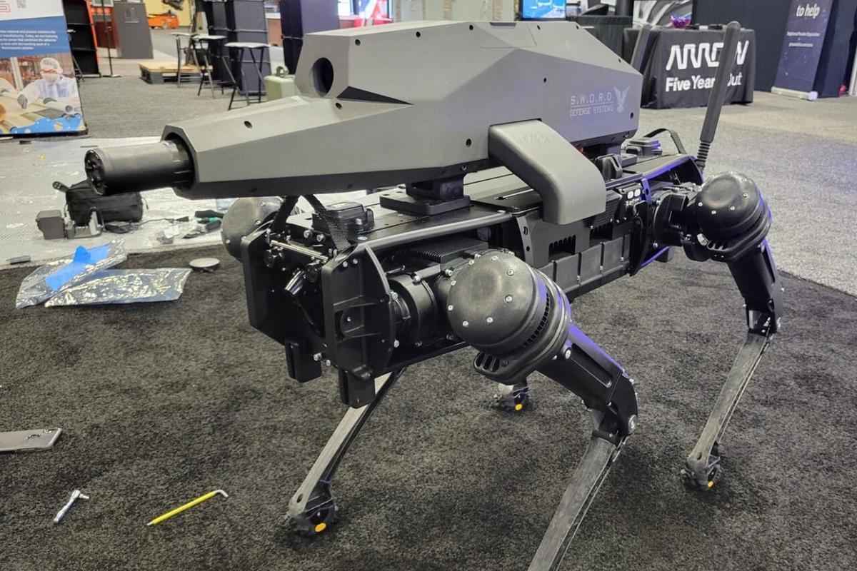 Ghost Robotics presented a back-mounted gun attachment by Sword Defense Systems for its Vision 60 robot at the NDIA Future Force Capabilities expo in Georgia