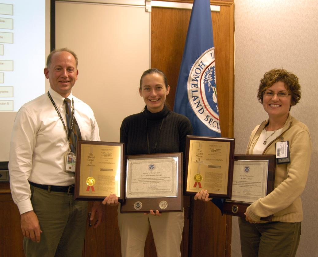 Adam Hutter, Director of NUSTL, presents Cecilia Murtagh (center) and Gladys Klemic with plaques commemorating Homeland Security's first patent, for the Citizen's Dosimeter (Photo: Jenny May)