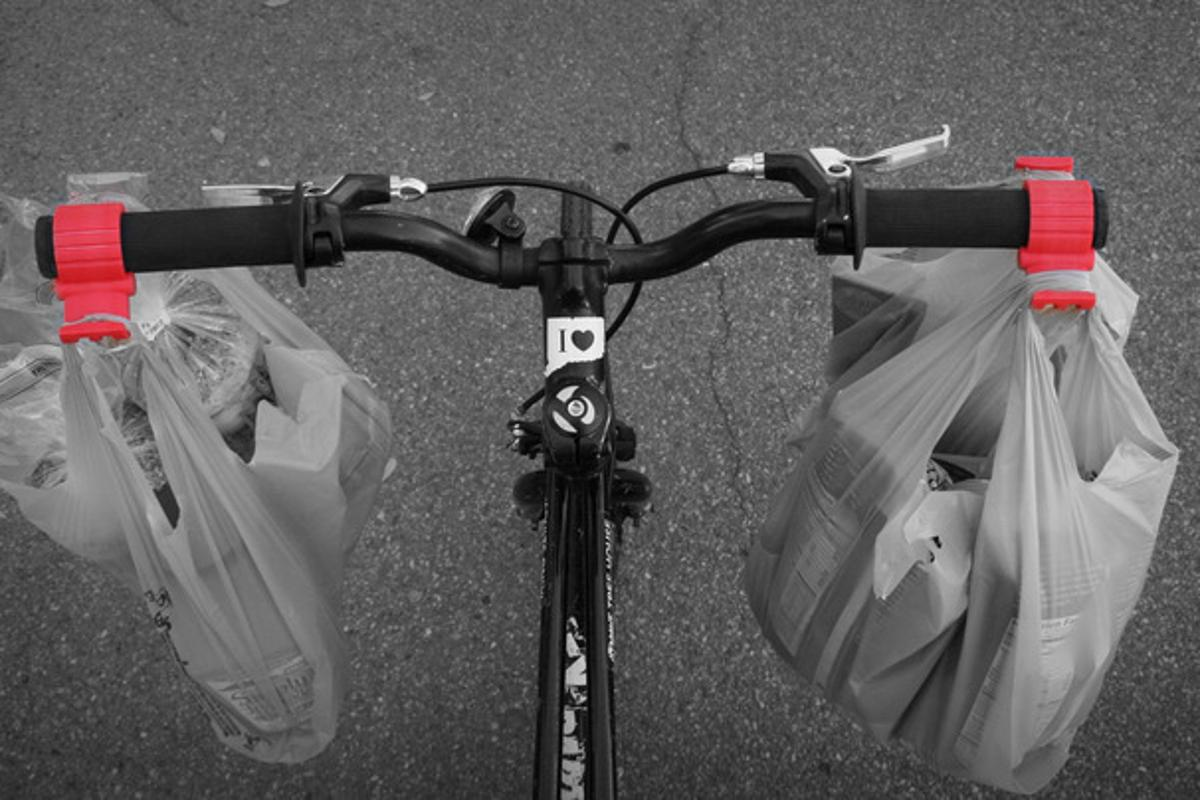 The Bag Buddy is a simple handlebar clamp designed to make carrying shopping bags on a bicycle easier