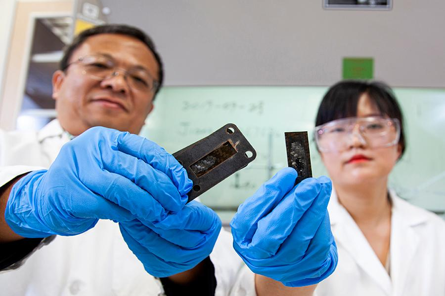 Professor Zhiyong (Richard) Liang Ph.D. , left, a professor and director of the High-Performance Materials Institute (HPMI) and Industrial and Manufacturing engineering research faculty member in Ayou Hoa, Ph.D. look over carbon fiber polymer coated with a protective heat shield made of a carbon nanotube sheet that was heated to a temperature of 1900º centigrade
