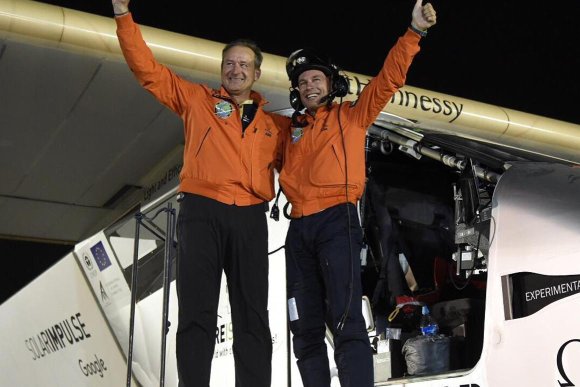 Andre Borschberg (L)andBertrand Piccard celebrateafter Solar Impulse 2 touches down in Abu Dhabi