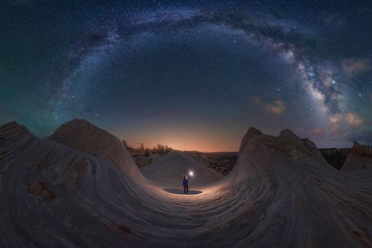 Good Night Utah, shot in Kanab, Utah, USA. Waves of rock mimic the arch of the Milky Way overhead, forming a makeshift circle. The Sun begins to peek over the horizon, the same color as the light cast by the figure in the center.