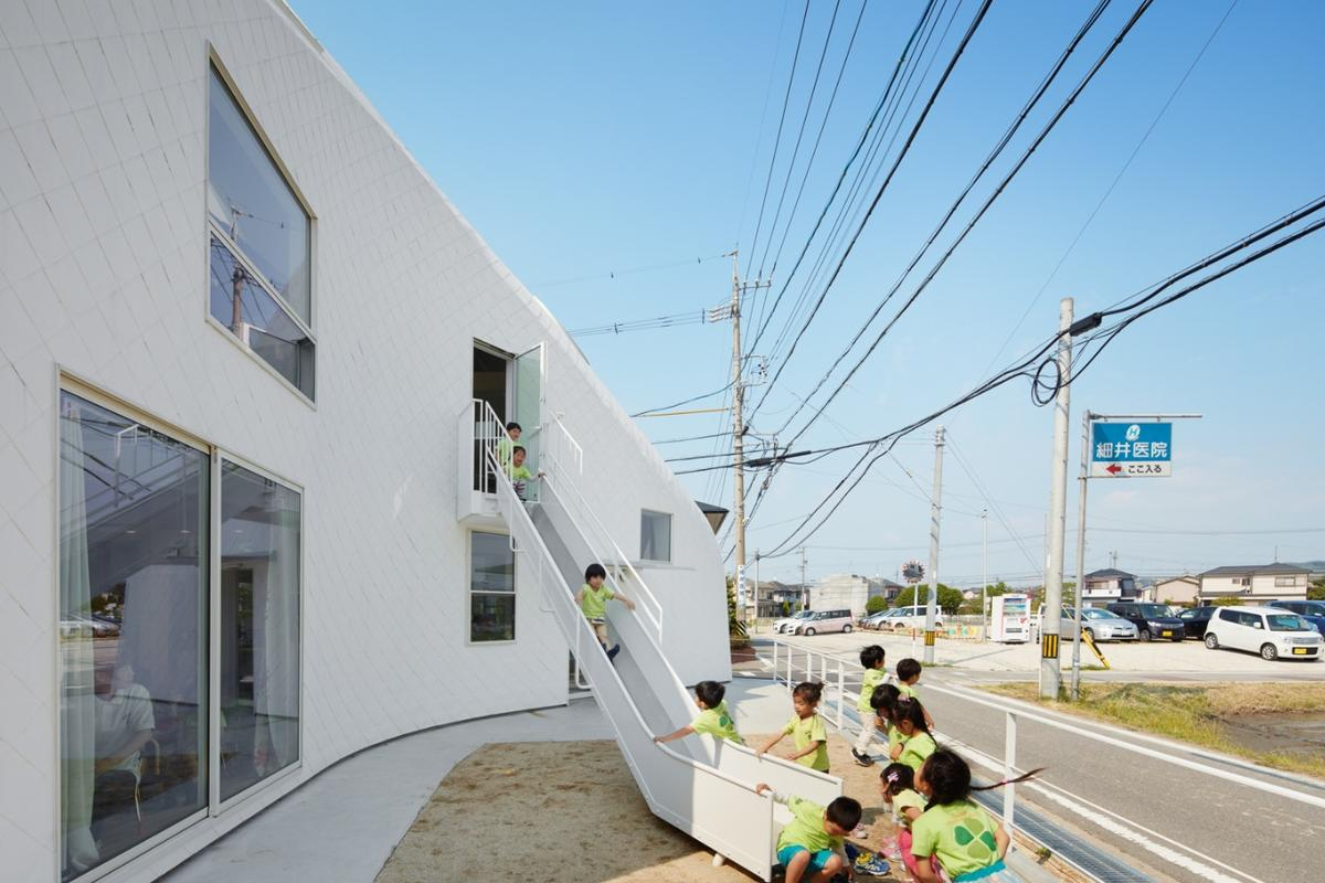 A slide descends from the upstairs floor to an outdoor play area in front of the building