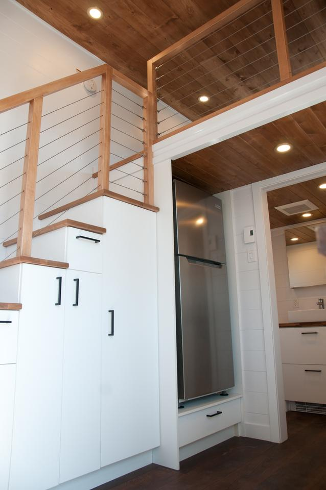 The kitchen includes a fridge/freezer, which is installed into the storage-integrated staircase