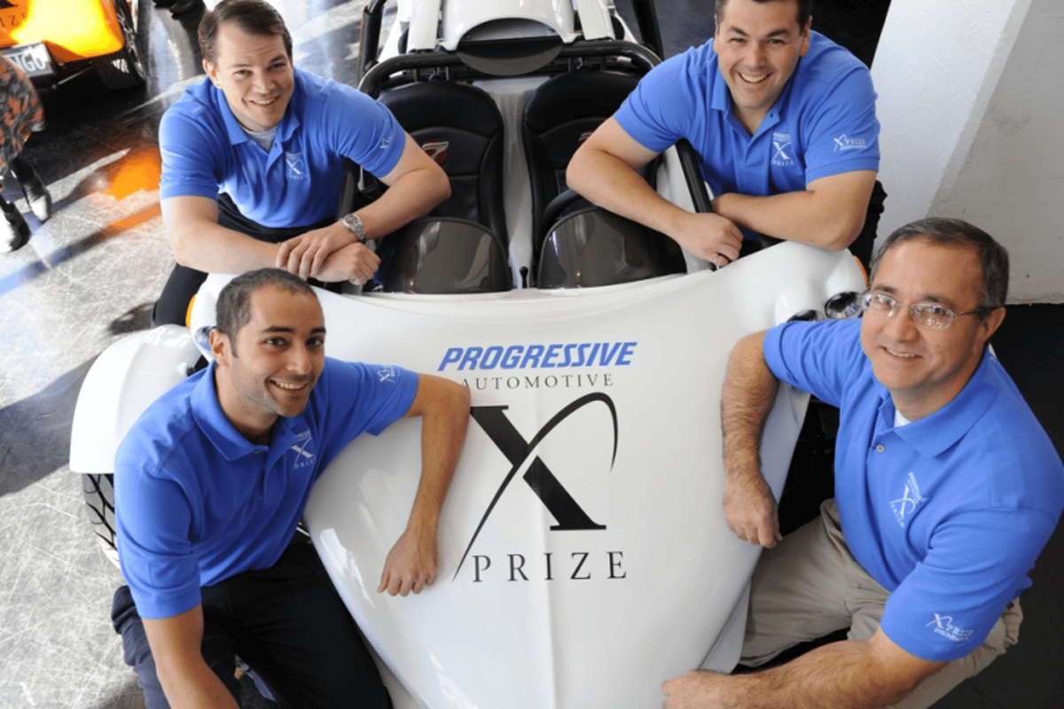 Team OptaMotive members (clockwise from top right: Mark Demers, Mike Nispel, Murat Ozkan and Michael Worry) with their E-Rex electric vehicle which has qualified for the next round in the Progressive Insurance Automotive X Prize competition