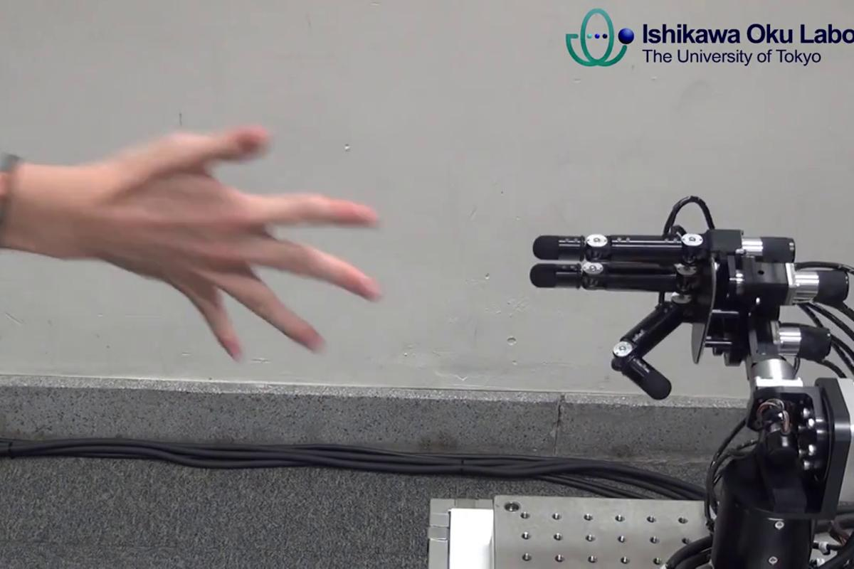 The Ishikawa Oku Lab's robot hand sticks out two fingers (scissors), beating the human (paper) in about one millisecond
