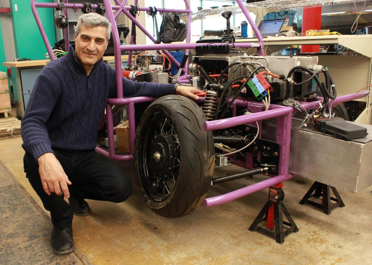 Prof. Amir Khajepour poses with a prototype three-wheeled vehicle that uses the new self-contained wheel units