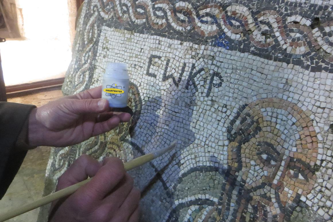 A man applies the SmartWater forensic solution to a mosaic in Syria