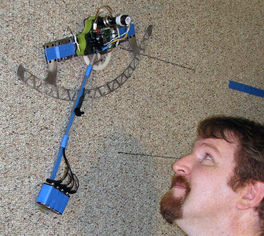 William Provancher watches as the efficient climbing robot he and colleagues developed scales a carpeted wall (Image: Mark Fehlberg, The University of Utah)