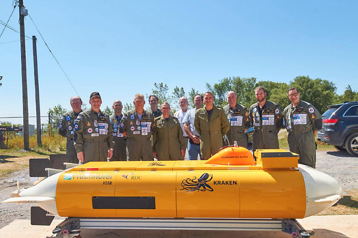 """The """"Raise the Arrow"""" team gathers for a photo behind the AUV"""