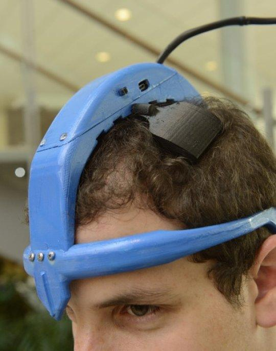David Blumenstyk models the STIMband non-invasive brain stimulator prototype for Parkinson's treatment that he co-created with four other Johns Hopkins students