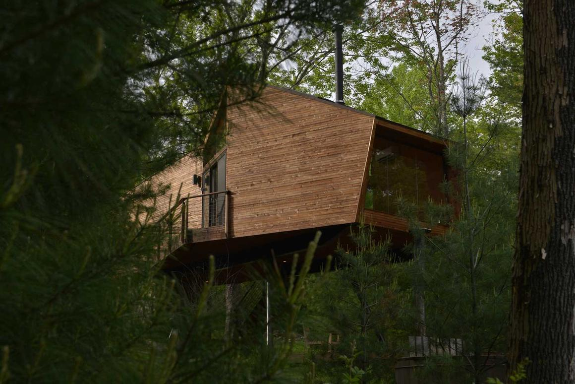 Built using locally sourced materials, the 69 sqm (743 sq ft) Inhabit Treehouse features a geometric structure made from reclaimed FSC timber