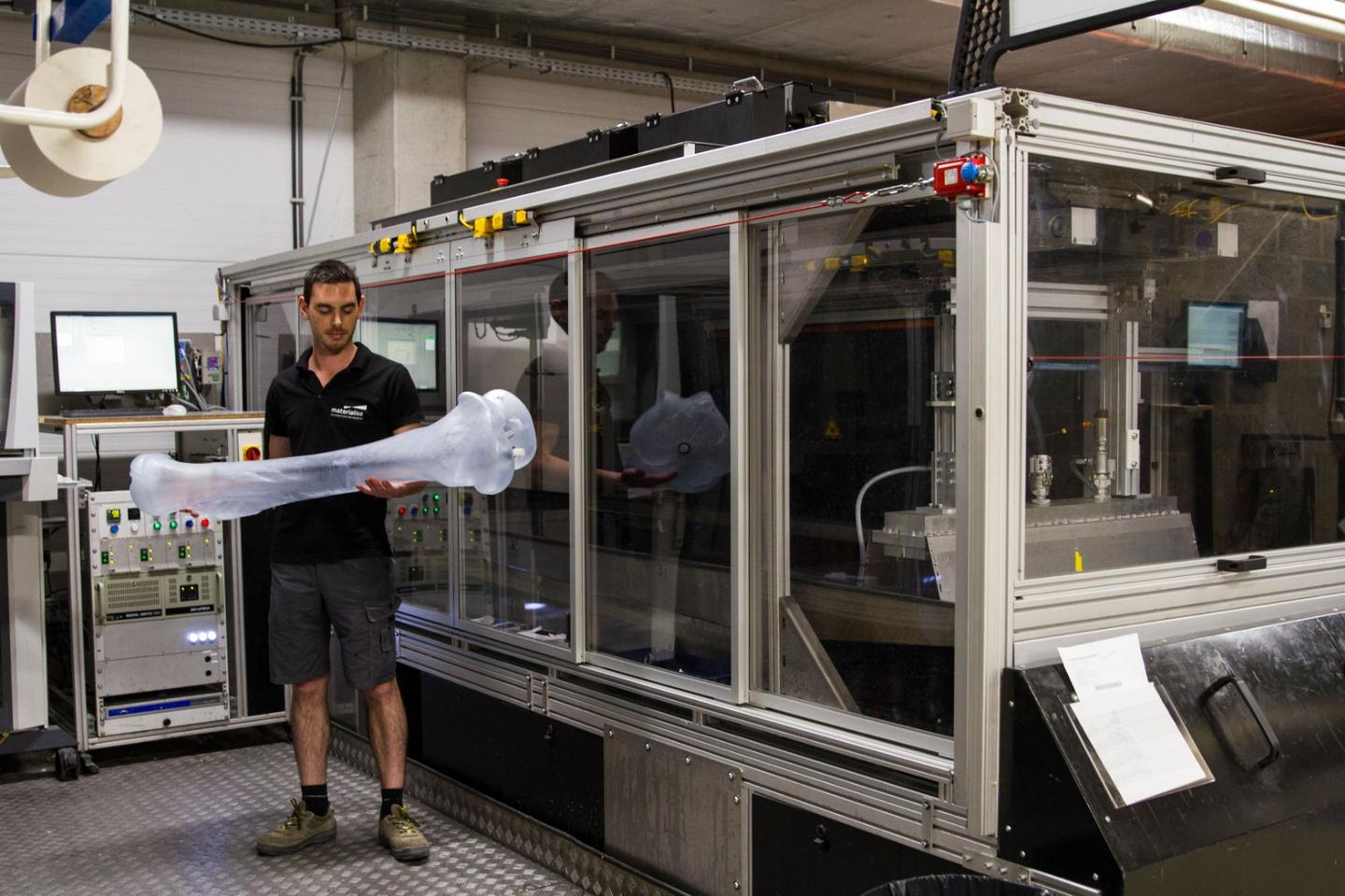 One of the 3D-printed mammoth bones, alongside one of the Mammoth Stereolithography large-format printers