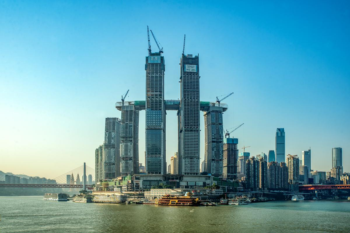 """Moshe Safdie's almost-complete Raffles City Chongqing includes a cluster of eight skyscrapers, plus a """"horizontal"""" skyscraper that serves as a skybridge"""