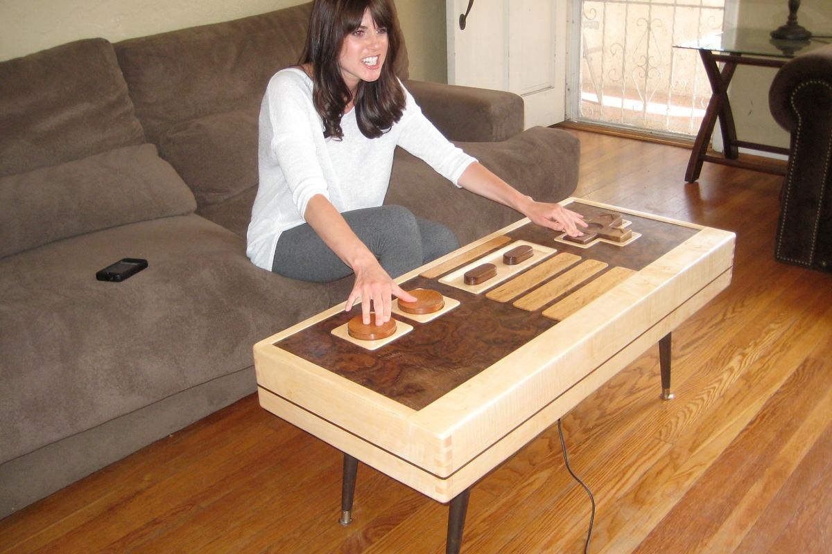 Charles Lushear has designed and built a coffee table that resembles a Nintendo Entertainment System controller, with buttons and a joypad that can actually control onscreen gaming action
