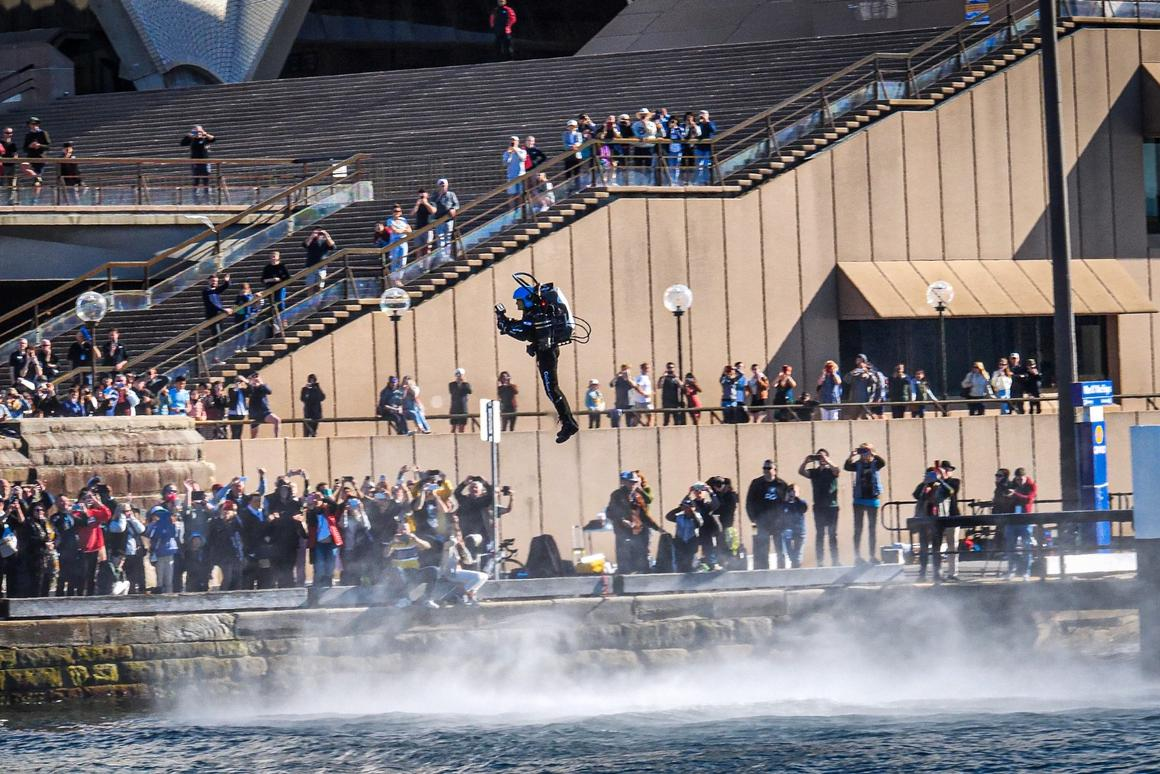 Ferocious jets whip up the water below David Mayman as crowds line the stairs of the Sydney Opera House