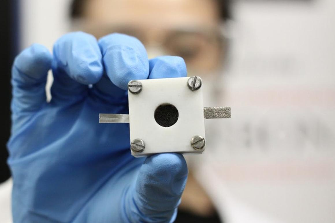 A researcher in Australia holds up a rechargeable zinc-air battery