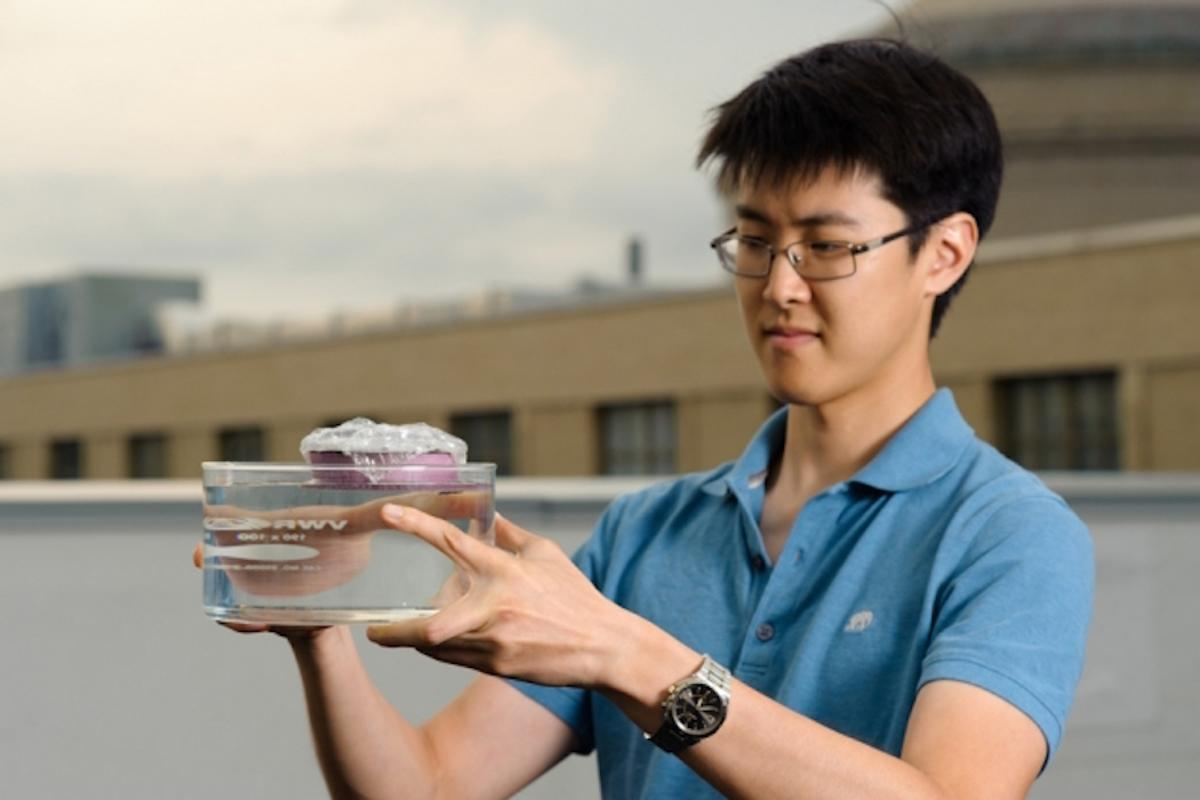 Graduate student and first author of the study George Ni holds the unique sponge-like device that can boil water through the absorption of sunlight