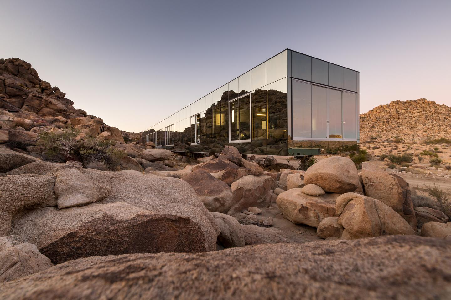 The Invisible House cantilevers over some rocks that were already on the site