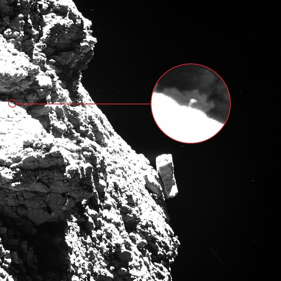 "In this Rosetta image, one of the Philae lander's ""feet"" can be seen protruding from behind an obscuring boulder to the upper left of the shot, appearing as a thin vertical line with a broad top"