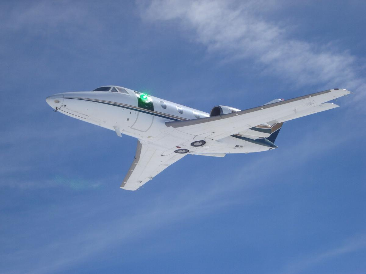 A green low-power laser beam passes through the turret on a research aircraft