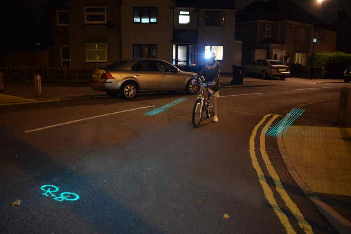 The Beacon Helmet laser-projects a green bicycle-warning symbol (seen at left) to let motorists know a bike is coming