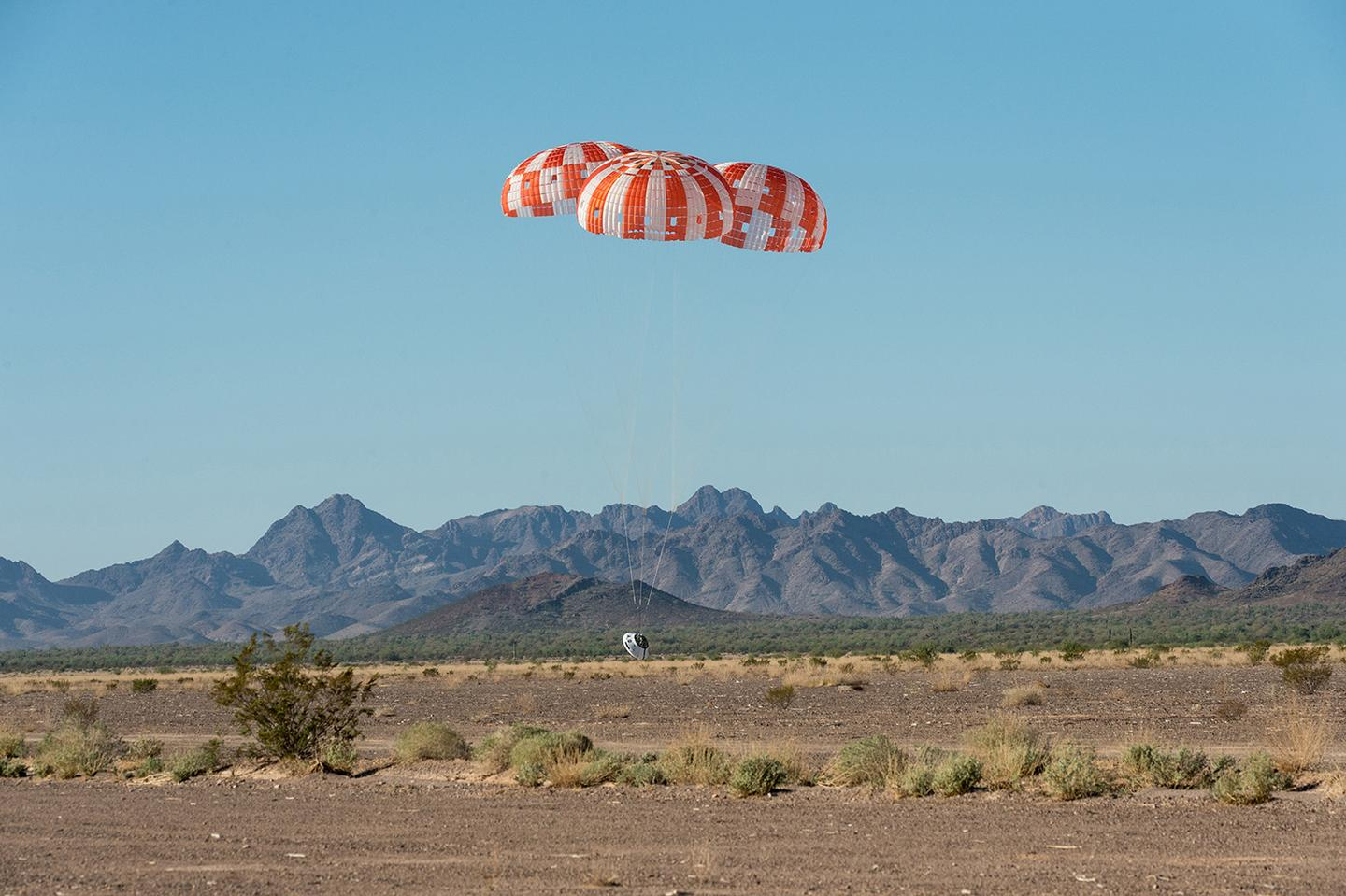 An Orion test capsule with its three main parachutes touches down in the Arizona desert on September 12, 2018