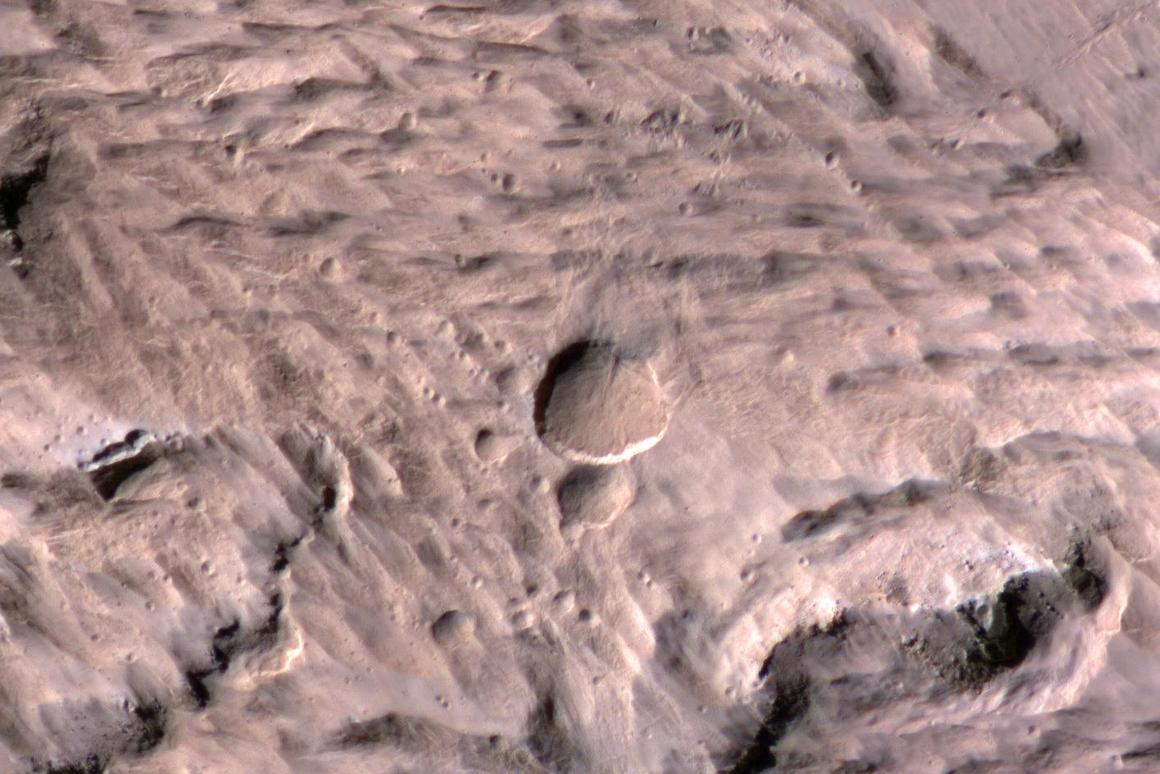 Large, fresh crater surrounded by smaller craters (Image: NASA)