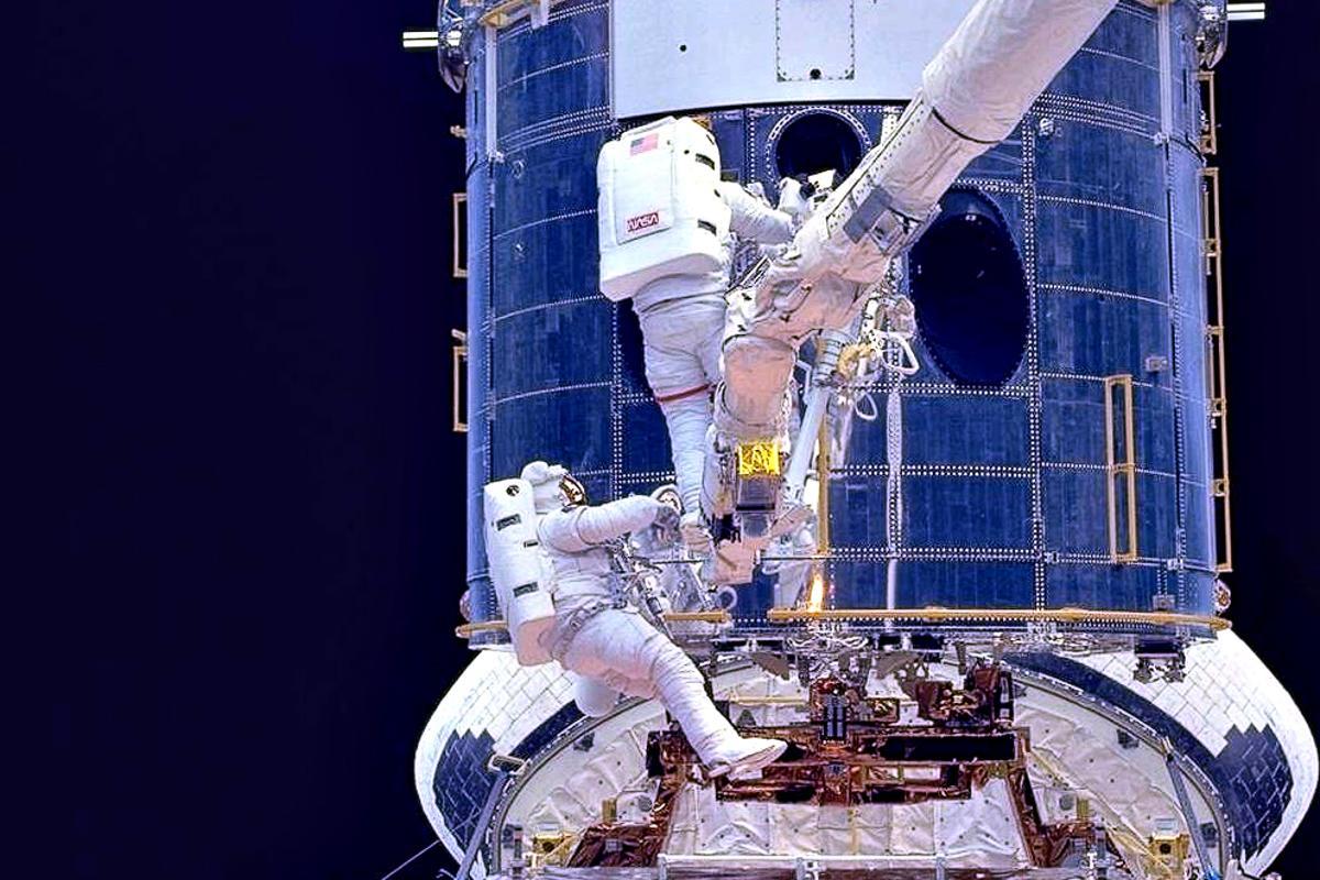 Astronauts fitting corrective optics to Hubble