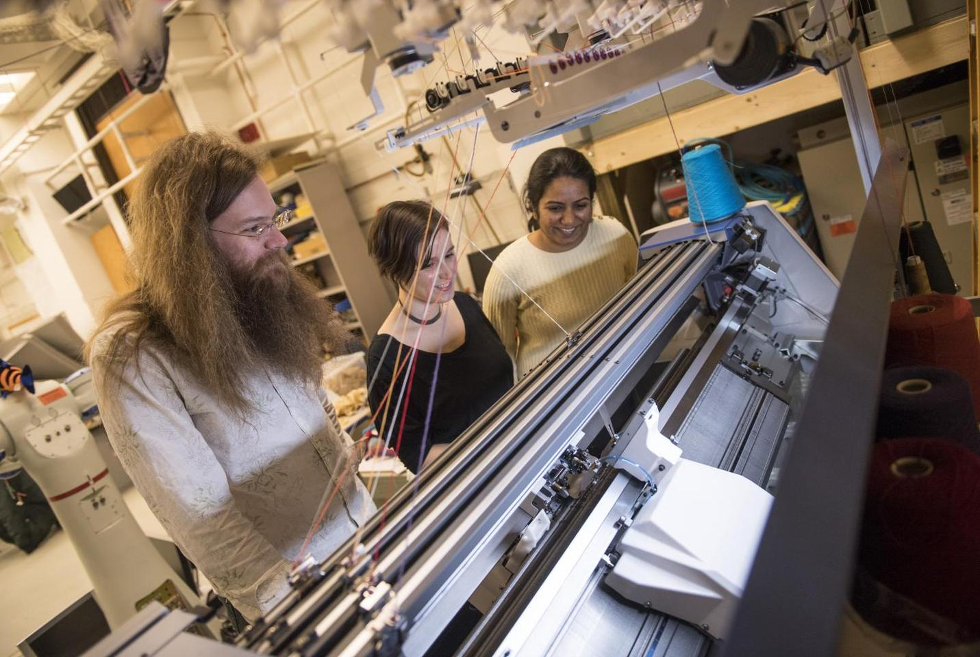 James McCann, Lea Albaugh and Vidya Narayanan watch a knitting machine work on a 3D shape
