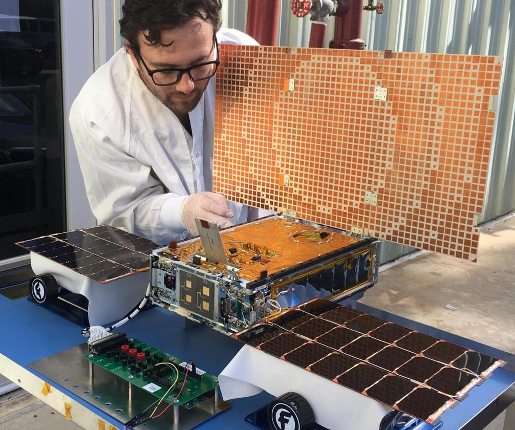Engineer Joel Steinkraus uses sunlight to test the solar arrays on one of the Mars Cube One (MarCO) spacecraft