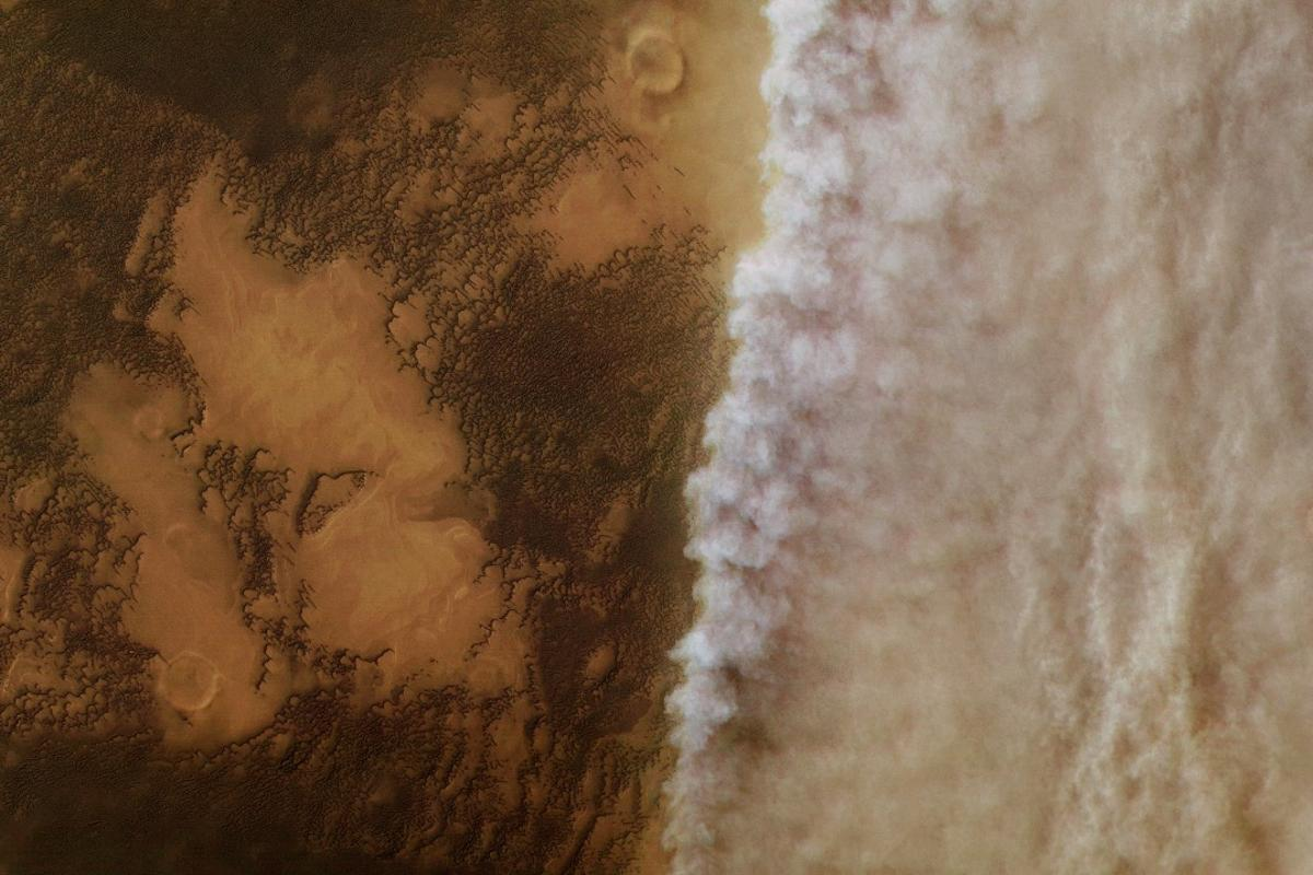 High resolution image from ESA's Mars Express showing dust clouds rolling over the Martian north polar cap