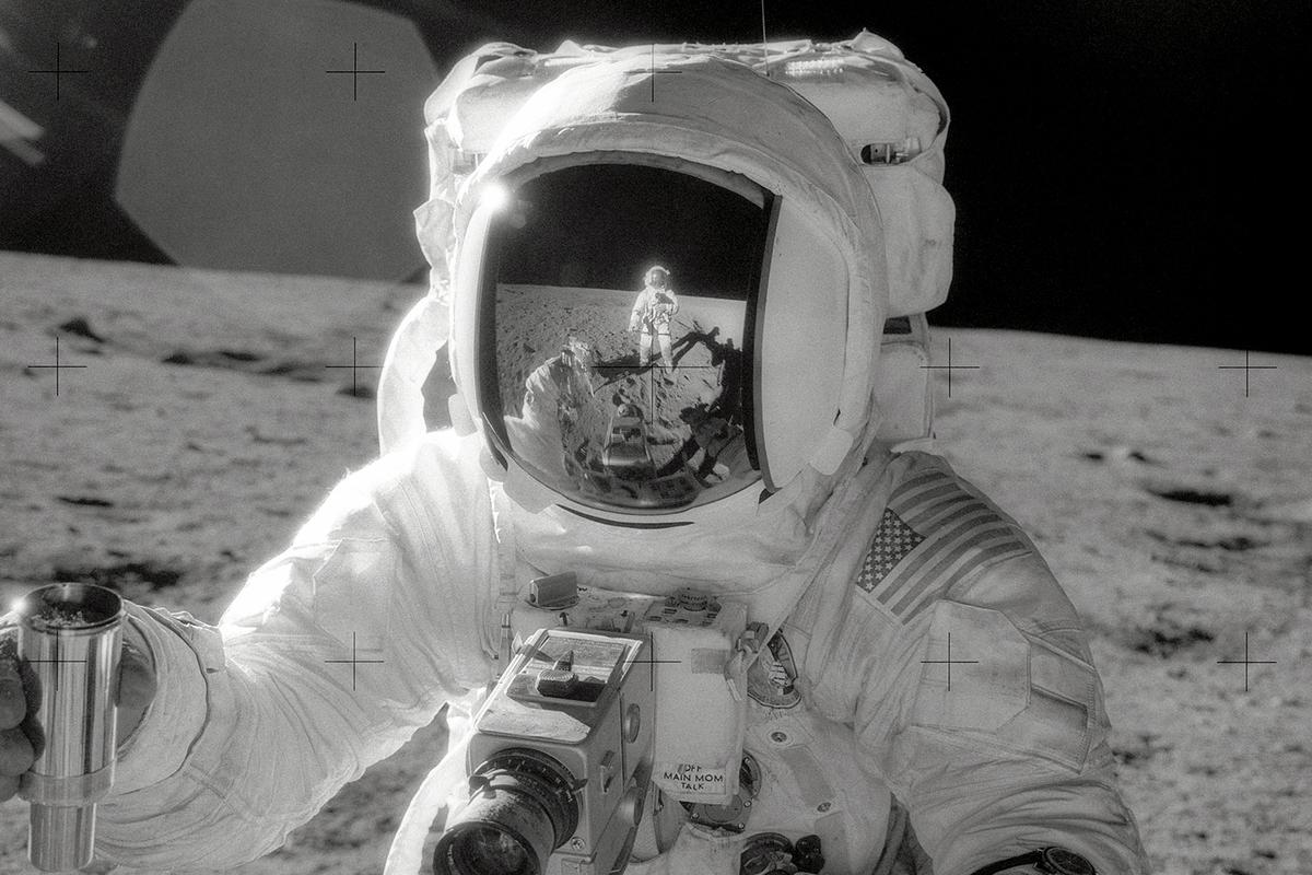 The Apollo 12 mission's Astronaut Alan L. Bean collecting a container of lunar soil
