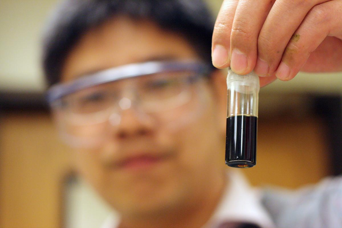 Peigao Duan, a University of Michigan graduate student, holds a vial of bio-oil