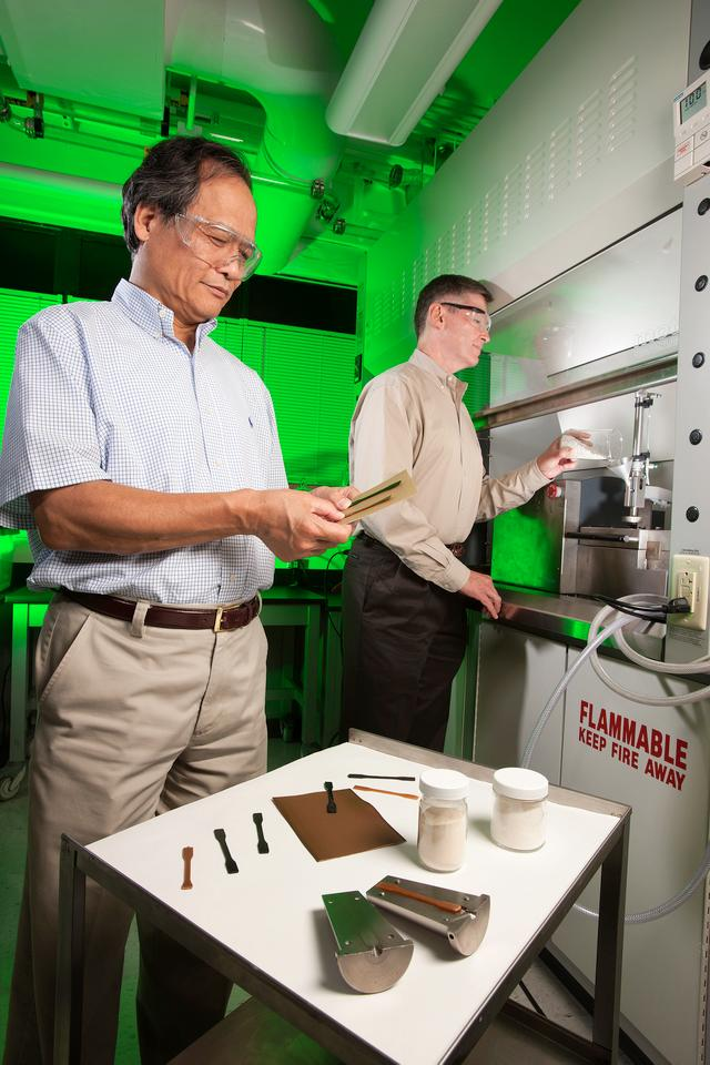 Plant physiologist Arland Hotchkiss (right) adds sugar beet pulp and polylactic acid to an extruder to make the bioplastic strips that chemist LinShu Liu is inspecting