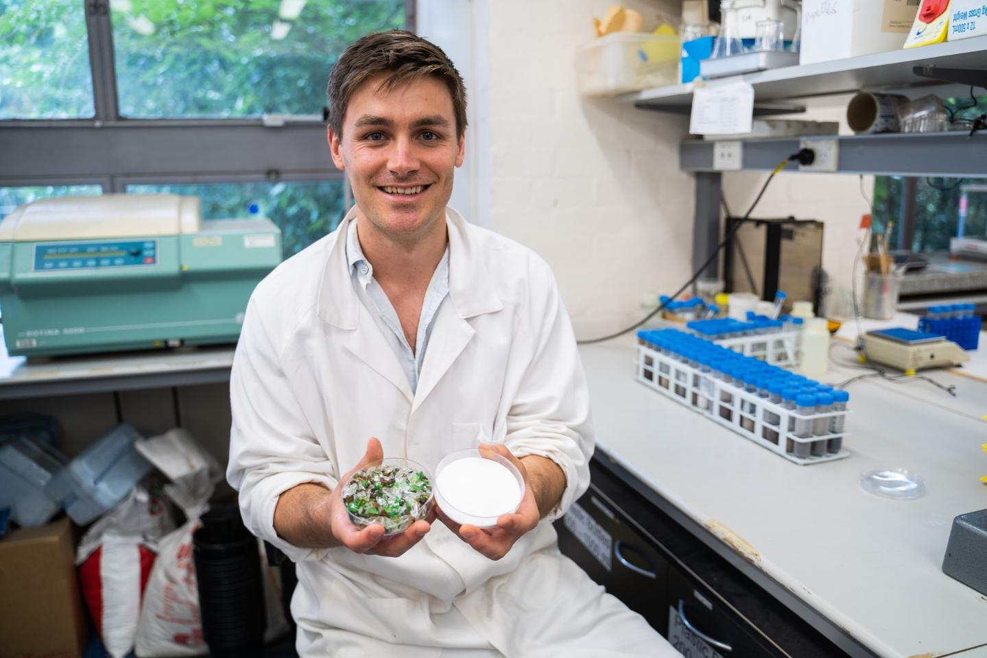 PhD candidate Rhys Pirie with glass dishes containing waste glass and the silicate end product