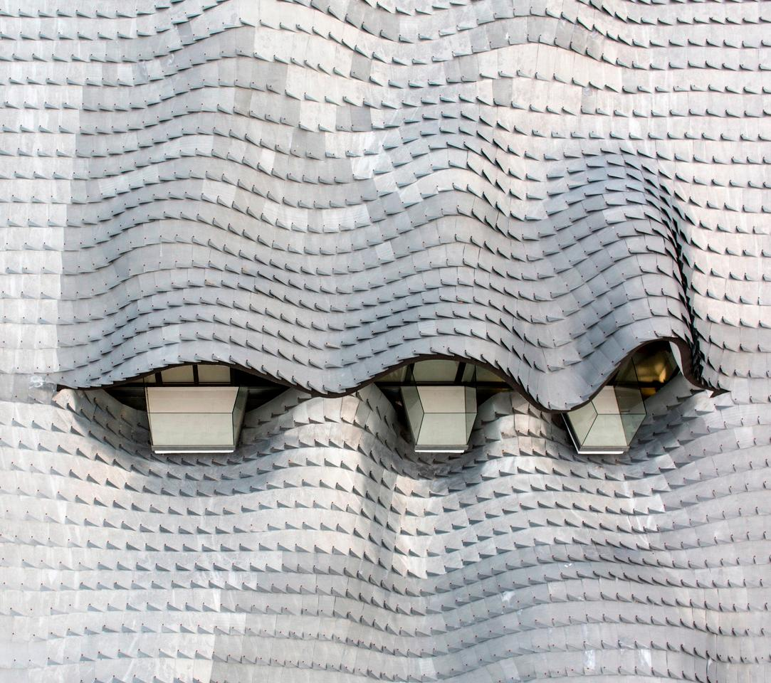 The roof comprises a double curved concrete shell packed with insulation and clad in handmade (and hand-placed) zinc roof tiles