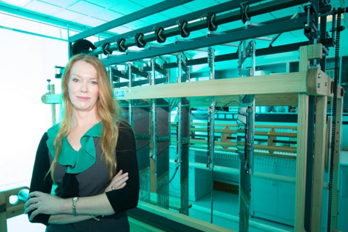 """Professor Melissa Knothe Tate with the computer-controlled jacquard loom used to create a """"smart"""" fabric that mimics the properties of periosteum"""