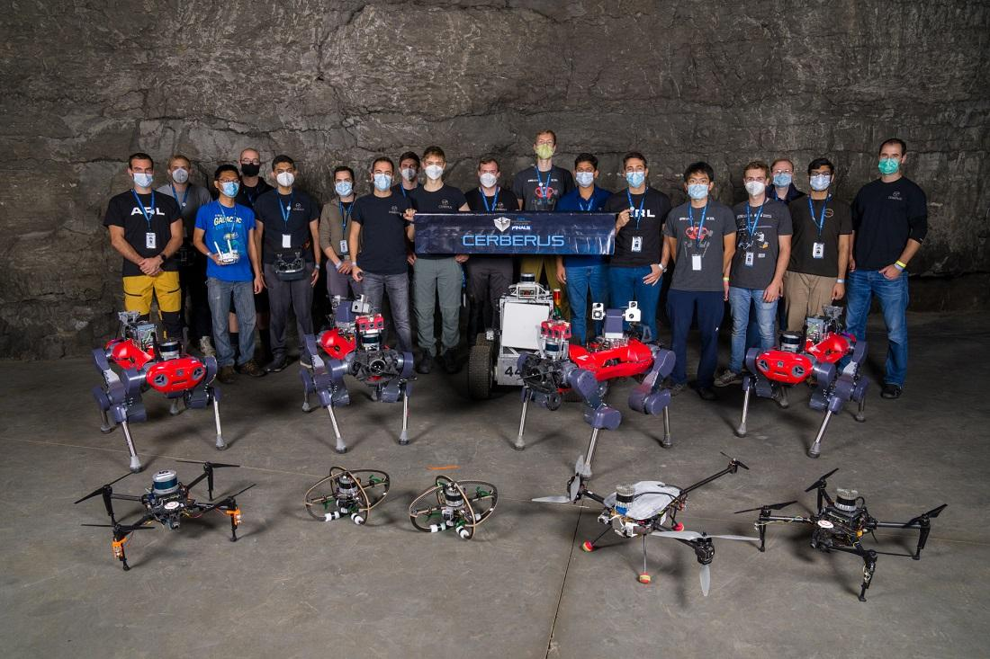 The Team CERBERUS members with their multicopter drones and ANYmal C quadruped robots