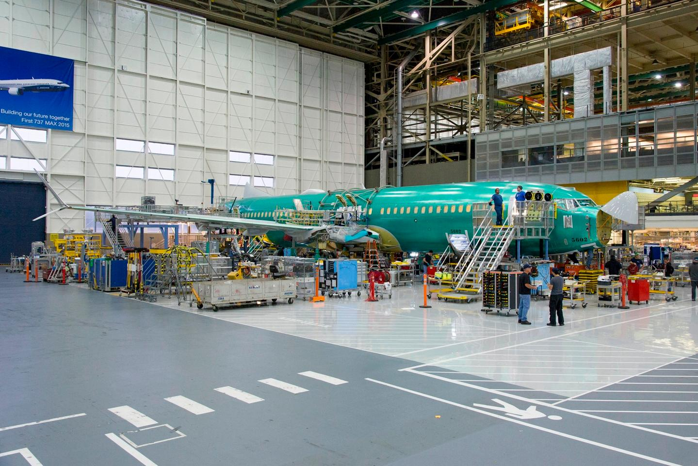 Mechanics attach the wings to the body of the 737 MAX