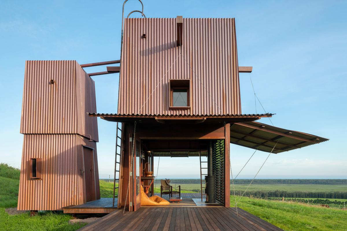 Australian architectural studio Casey Brown Architecture has recently completed an unusual corrugated copper tiny homeThe unique structure resembles a two-story tower and boasts external sides that open up the home to the outdoors, while doubling as overhead verandas