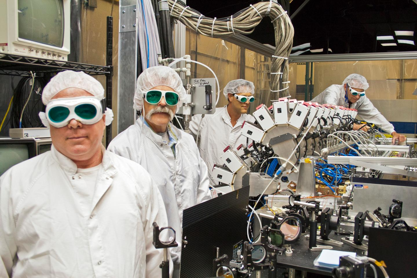 Boeing Thin Disk Laser engineers and the laser's main optical bench (Photo: Boeing)