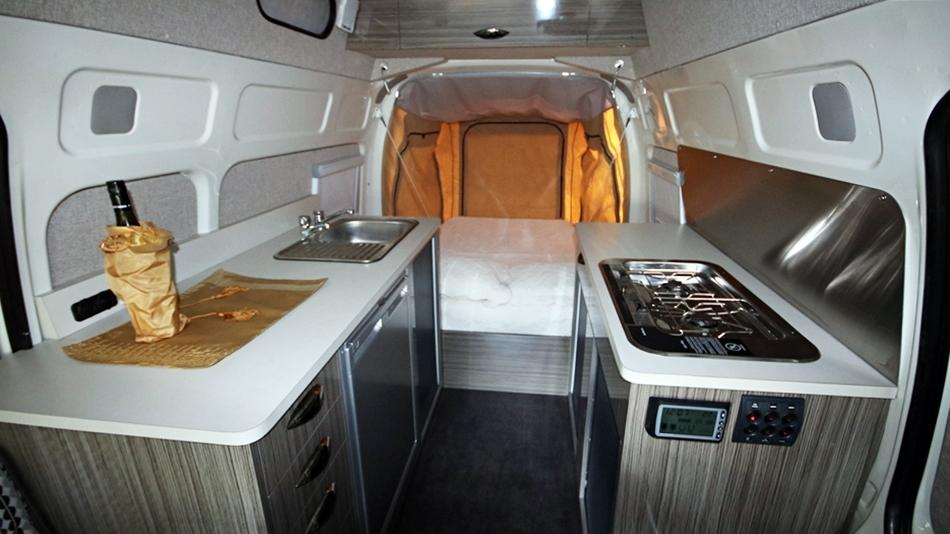With the bed pushed out the back of the van, Bus 4x4 is able to give the camper van a large kitchen area and full-time dining lounge