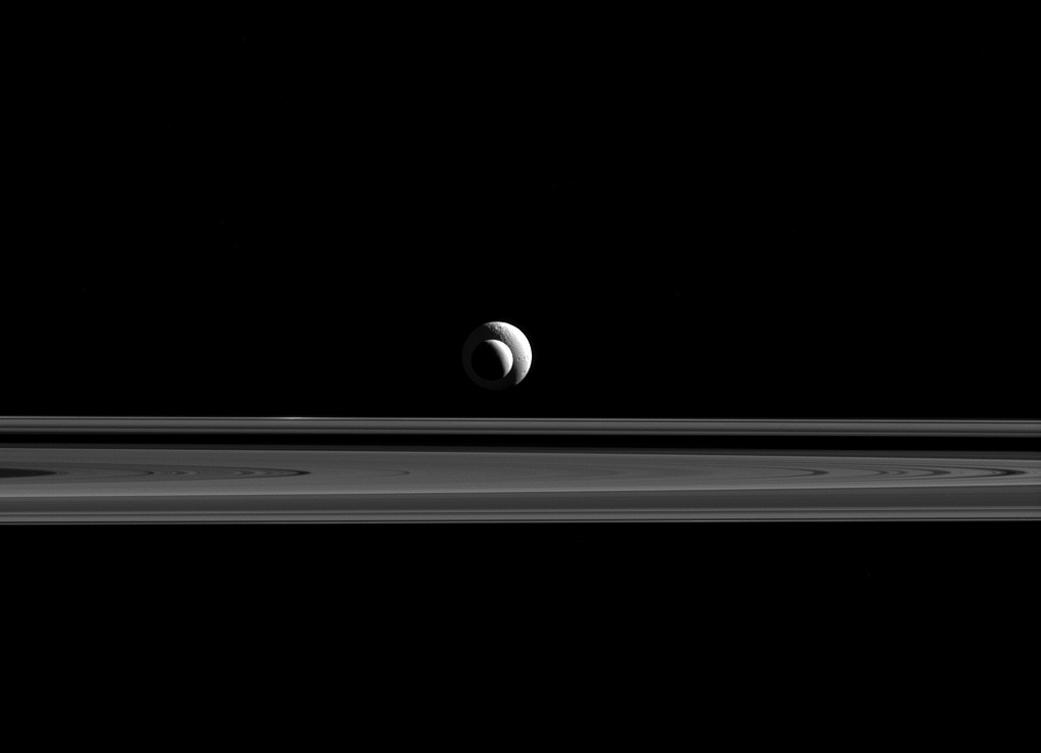 In the new image, Cassini captures Enceladus passing in front of Tethys